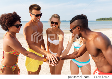 happy friends stacking hands on summer beach 44261202