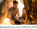 family with tablet pc in kids tent at home 44261249