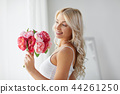 woman in underwear with bunch of flowers at window 44261250