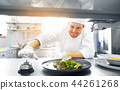 happy male chef cooking food at restaurant kitchen 44261268