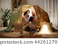 happy couple with tablet pc in kids tent at home 44261270