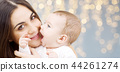 mother with baby over festive lights background 44261274