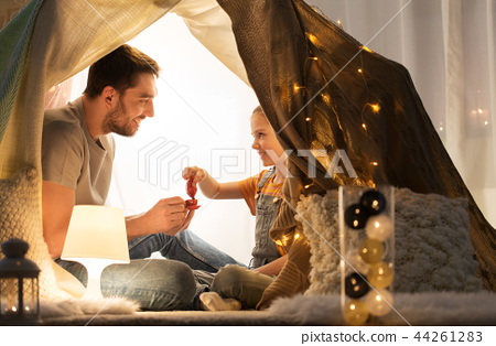 family playing tea party in kids tent at home 44261283