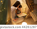 happy family reading book in kids tent at home 44261287