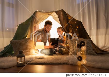 family with tablet pc in kids tent at home 44261304