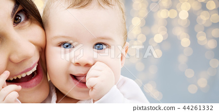 mother with baby over festive lights background 44261332