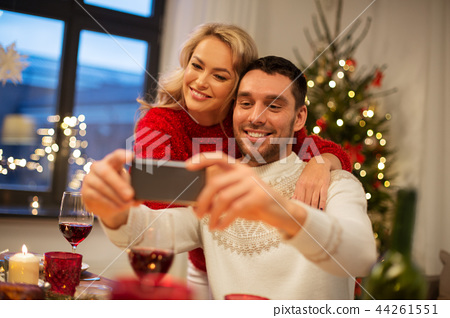 happy couple taking selfie at christmas dinner 44261551