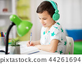 boy in headphones with textbook learning at home 44261694