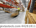 worker carrying loader with goods at warehouse 44261811
