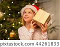 smiling girl in santa hat with christmas gift 44261833