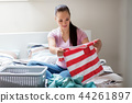 woman or housewife sorting laundry at home 44261897