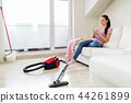 woman with vacuum cleaner drinking coffee at home 44261899