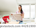 woman taking bath towels from drying rack at home 44261900