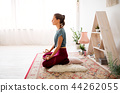 woman meditating in lotus pose at yoga studio 44262055