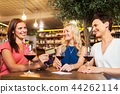 women with credit card at wine bar or restaurant 44262114