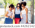 happy women showing shopping bags in city 44262142