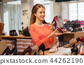 happy young woman choosing shoes at store 44262196