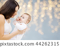 mother with baby over festive lights background 44262315