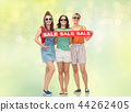 teenage girls with sale banner over festive lights 44262405