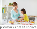 happy mother and daughter cooking cupcakes at home 44262424