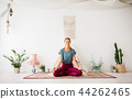 woman meditating in lotus pose at yoga studio 44262465