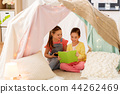 little girls reading book in kids tent at home 44262469