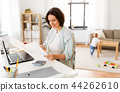 mother working with papers and baby boy at home 44262610