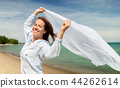 happy woman with shawl waving in wind on beach 44262614