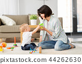 happy mother giving sippy cup to baby son at home 44262630