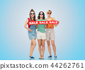 happy female friends with sale banner over blue 44262761