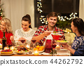 happy friends having christmas dinner at home 44262792