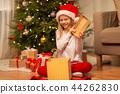 smiling girl in santa hat opening christmas gift 44262830