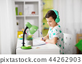 boy in headphones with textbook learning at home 44262903