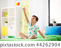 happy little boy playing with airplane toy at home 44262904