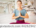 woman meditating in lotus pose at yoga studio 44262942