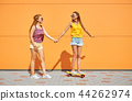 teenage girls riding skateboard on city street 44262974