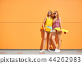 teenage girls with short skateboards in city 44262983