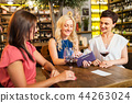 women paying bill at wine bar or restaurant 44263024