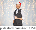 happy man in santa hat and suit on christmas 44263158