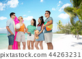 friends with beach supplies over exotic landscape 44263231