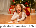 smiling girl writing christmas wish list at home 44263263