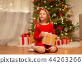 smiling girl with christmas gift at home 44263266