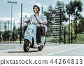 Optimistic male student capping to university on motorbike 44264813