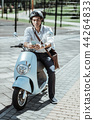 Smart male student checking messages on motorbike 44264833
