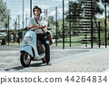 Reflective male student typing friends on motorbike 44264834