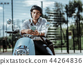 Pensive male student checking schedule on motorbike 44264836