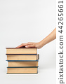hand on a pile of books 44265661