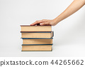 hand on a pile of books 44265662