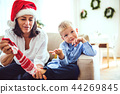 A small boy and grandmother with a Santa hat sitting on a sofa at home at Christmas time. 44269845