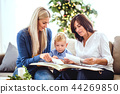 A small boy with mother and grandmother looking at photos at home at Christmas time. 44269850